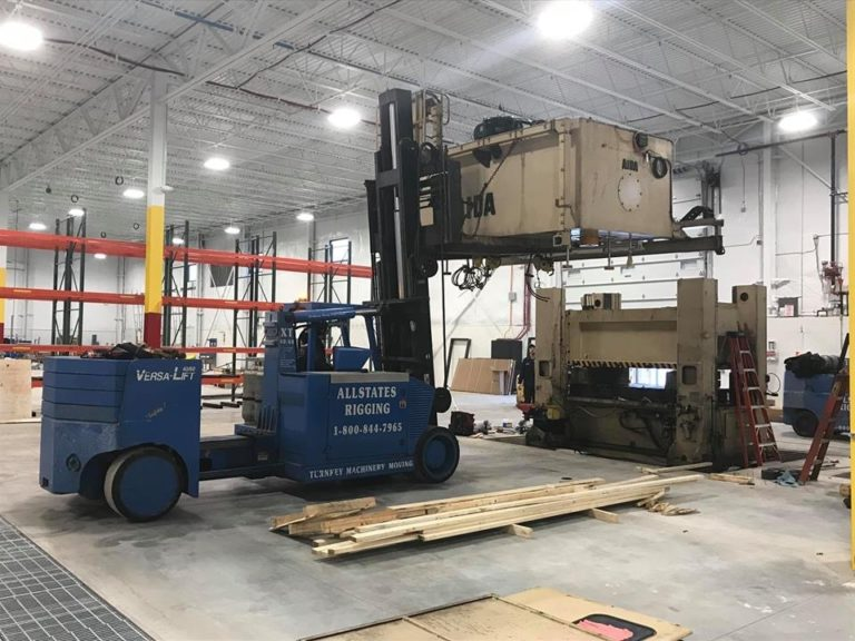 Versa-Lift Forklift lifting a machine on top of another machine